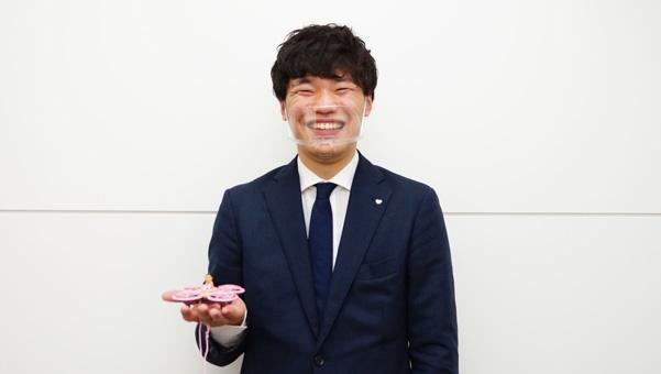 カプドローンを手に持つ﨑本さんの写真